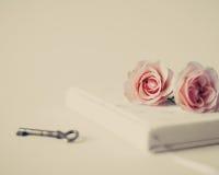 Weinlesenotizbuch und -rosen Stockbild