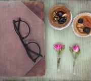 Weinlesenotizbuchspott oben für Grafik mit rosa Rosen und Kuchen Platz für Text Frische Blumen und schwarze Gläser Lizenzfreie Stockfotografie