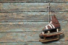 Weinlesepaare Schlittschuhe, die an einer gebrochenen Farbenwand hängen Stockfotografie