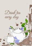 Weinleseplakat mit Teekanne und Schale und Blumen des Singrüns auf braunem Hintergrund Lizenzfreies Stockfoto