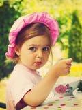 Weinleseporträt des kleinen Mädchens isst mit Appetit lizenzfreies stockbild