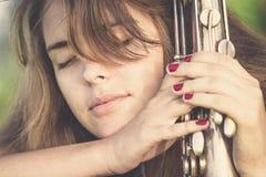 Weinleseporträt der jungen Frau mit Musikinstrument des Winds in der Hand auf dem Rasen Lizenzfreies Stockbild