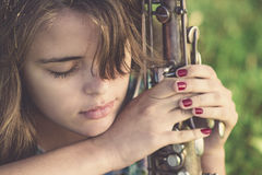 Weinleseporträt des halben Gesichtes einer jungen Frau mit Musikinstrument des Winds in der Hand auf dem Rasen Lizenzfreie Stockfotografie