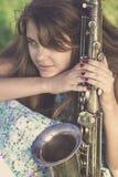 Weinleseporträt des halben Gesichtes einer jungen Frau mit Musikinstrument des Winds in der Hand auf dem Rasen Stockbild