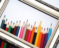 Weinleserahmen für Malereien und farbige Bleistifte auf einem weißen Hintergrund stockfoto