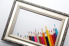 Weinleserahmen für Malereien und farbige Bleistifte auf einem weißen Hintergrund lizenzfreies stockfoto