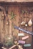 Weinlesereisestillleben auf altem Bretterzaun mit Seil, Starfish, Kompass, Holzschildern und Zubehör Stockbild