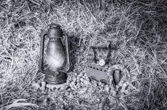 Weinleserot beleuchtete Kerosinlampe und alte Sachen im Heu Stockbilder