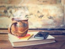 Weinleseschale mit heißen Getränken und Dampf, T-Stück oder Kaffee auf altem Buch mit Smarttelefon stockfotografie