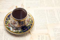 Weinleseschale starker aromatischer Kaffee auf dem Hintergrund von Druckschriften des alten Buches Stockfotos