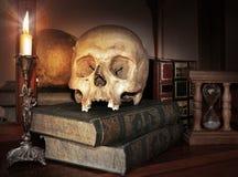 Weinleseschädel auf antikem Buch mit Kerze und Sanduhr Stockfotografie