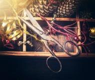 Weinleseschere auf Holzkiste mit Weihnachtsdekoration, Retro- getont Stockfotos