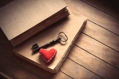 Weinleseschlüssel mit Herzform und alten Büchern Lizenzfreies Stockbild