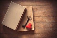 Weinleseschlüssel mit Herzform und alten Büchern Stockbild