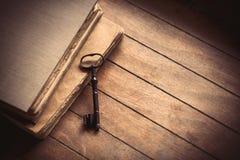 Weinleseschlüssel und alte Bücher auf Holztisch Lizenzfreies Stockfoto