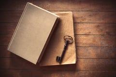 Weinleseschlüssel und alte Bücher auf Holztisch Stockbild