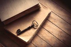Weinleseschlüssel und alte Bücher auf Holztisch Stockfotografie