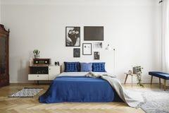 Weinleseschlafzimmerinnenraum mit Nachttisch, Königgrößenbett mit blauer Bettwäsche und Kissen Modellgalerie auf der weißen Wand stockfotografie
