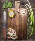 Weinleseschneidebrett mit Bestandteilen für das Kochen, Knoblauch, Zwiebelringe, Frühlingszwiebeln ölen Messerplatz für Text, Rah Stockfotografie