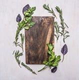Weinleseschneidebrett mit Kräutern auf hölzernem rustikalem Draufsicht-Abschlussplatz des Hintergrundes für Text, Rahmen Stockfoto
