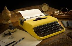 Weinleseschreibmaschine über einem alten hölzernen Schreibtisch mit altem stationärem Lizenzfreie Stockbilder