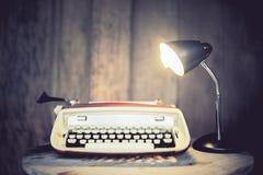 Weinleseschreibmaschine mit Lampe auf rundem Holztisch Lizenzfreie Stockfotos