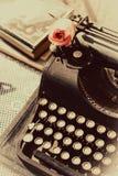Weinleseschreibmaschine mit Rosarose, alte Bücher auf Tabelle Stockfoto