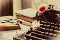 Weinleseschreibmaschine mit Rosarose, alte Bücher auf Tabelle Lizenzfreie Stockbilder