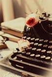 Weinleseschreibmaschine mit Rosarose, alte Bücher auf Tabelle Lizenzfreie Stockfotografie