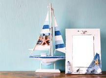 Weinleseseerahmen mit hölzernem Boot auf Holztisch Retro- gefiltertes Bild Lizenzfreie Stockbilder