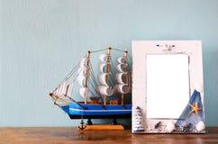 Weinleseseerahmen mit hölzernem Boot auf Holztisch Retro- gefiltertes Bild Stockfotografie