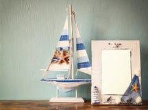 Weinleseseerahmen mit hölzernem Boot auf Holztisch Retro- gefiltertes Bild Lizenzfreies Stockbild