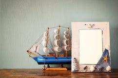 Weinleseseerahmen mit hölzernem Boot auf Holztisch Retro- gefiltertes Bild Lizenzfreie Stockfotografie