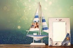Weinleseseerahmen mit hölzernem Boot auf Holztisch und Funkelnhintergrund Stockbilder