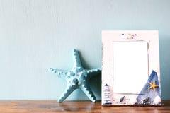 Weinleseseerahmen mit Starfish auf Holztisch Retro- gefiltertes Bild Lizenzfreie Stockbilder