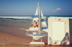 Weinleseseerahmen mit Starfish auf Holztisch und Meer setzen Hintergrund auf den Strand Retro- gefiltertes Bild Stockbild