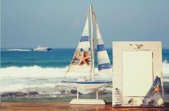 Weinleseseerahmen mit Starfish auf Holztisch und Meer setzen Hintergrund auf den Strand Retro- gefiltertes Bild Lizenzfreies Stockbild