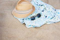 Weinlesesommer-Weidenstrohhut mit buntem Band, blauer Decke des Strandes, pareo und Sonnenbrille auf dem Strand stockfotografie