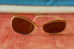Weinlesesonnenbrille auf braunem hölzernem Hintergrund Lizenzfreie Stockbilder