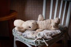 Weinlesespielzeugkaninchen Weiche Spielzeughasen der alten Weinlese, die im alten weißen Stuhl liegen lizenzfreie stockfotos
