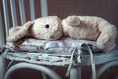 Weinlesespielzeugkaninchen Weiche Spielzeughasen der alten Weinlese, die im weißen Stuhl der Weinlese liegen lizenzfreie stockfotografie