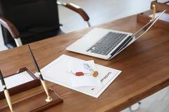 Weinlesestempel, -laptop und -dokumente auf Schreibtisch stockbilder