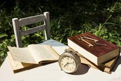 Weinlesestillleben mit altem Wecker, Schlüsseln und Büchern lizenzfreie stockfotos
