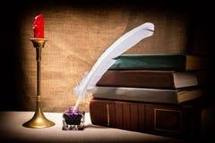 Weinlesestillleben mit alten Büchern nähern sich Schreibtischgarnitur, Feder und Kerze im Kerzenständer auf Segeltuchhintergrund  Lizenzfreie Stockfotografie