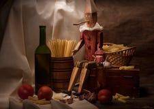 Weinlesestillleben mit Spaghettis und Pinocchio Stockbilder