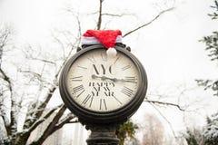 Weinlesestraßenuhr mit Hut Aufschrift guten Rutsch ins Neue Jahr NYC und Santa Clauss auf ihnen draußen im Winter Lizenzfreies Stockfoto