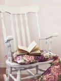 Weinlesestuhl mit Kissen und Buch Stockbild
