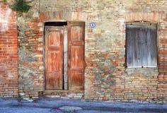 Weinlesetür und -fenster im Ziegelsteinhaus, Italien. lizenzfreies stockfoto