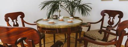 Weinlesetabelle für das Tee-Trinken und die Holzstühle Stockfotografie