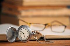 Weinlesetaschen-Uhrgläser und öffnen altes Buch Stockfotos